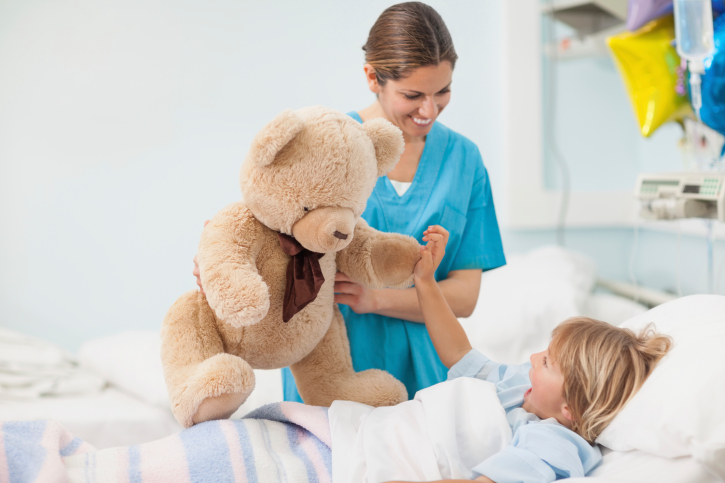 Nurse showing a teddy bear to child